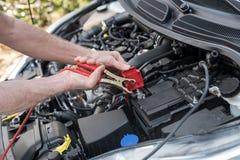Hands of car mechanic using car battery jumper cable. Hands of car mechanic using cables to start a car engine Stock Photos