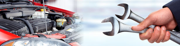 Hands of car mechanic with wrench in garage. Stock Images