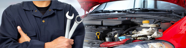 Hands of car mechanic with wrench in garage. Royalty Free Stock Photos