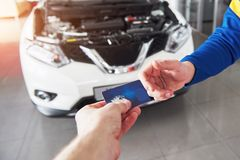 Hands of car mechanic with wrench in garage, payment by credit card