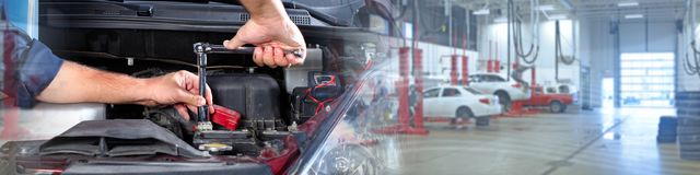 Car mechanic. Hands of car mechanic with wrench over garage background Royalty Free Stock Photo