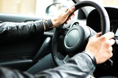 Hands on car steering wheel. Close up view of a car steering wheel. Manual gearbox. Car interior details. Car transmission. Soft lighting. Abstract view Stock Photo