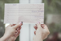 Hands with cardiogram. Female hands holding a heart cardiogram royalty free stock image