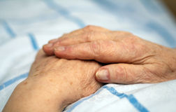 Hands of a care-dependent person. Old wrinkled hands of a care-dependent person lying in bed royalty free stock photography