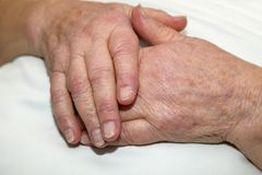 Hands of a care-dependent person. Old wrinkled hands of a care-dependent person lying in bed Royalty Free Stock Photo