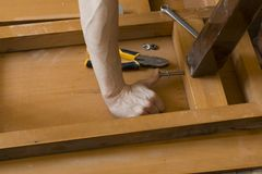 The hands of a carpenter assembling wooden furniture, Close-up stock image