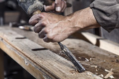 Hands of carpenter with chisel in the hands. On the workbench in carpentry stock photos