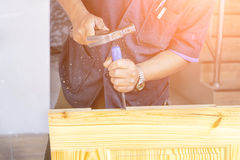 Hands of carpenter with chisel in the hands. On the workbench in carpentry Stock Images