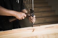 Hands of carpenter with chisel in the hands. On the workbench in carpentry royalty free stock photos