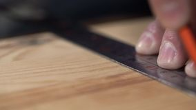 Hands of the carpenter draw a marking on a wooden board. Shot with Sony A7s and Canon lens macro 100mm stock video footage
