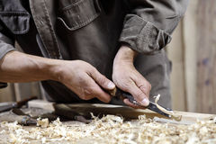 Hands of carpenter with a hammer and chisel on workbench in carpentry. Hands of carpenter with a hammer and chisel on the workbench in carpentry Stock Photos