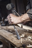 Hands of carpenter with a hammer and chisel Stock Images