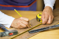 Hands of carpenter making measures Royalty Free Stock Photos