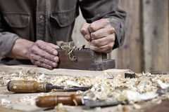 Hands of carpenter plane on workbench in carpentry Stock Image