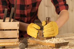 Hands of a carpenter planed wood, workplace royalty free stock photography