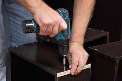 Hands carpenter with screwdriver, tighten screw in drawers of ch. Assembling furniture, Hands of a carpenter with a electric Cordless screwdriver, tighten the Stock Photo