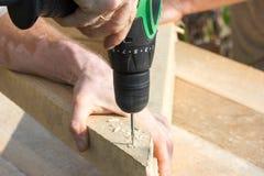 hands of a carpenter tightening an electric screwdriver screws into wood Stock Photos