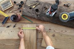 Hands Carpenter Work The Wood, Measuring With Tape Meter Old Rustic Wooden Boards, Top View With Tools On Background Stock Image