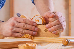 Hands of carpenter in work with woodworkers plane Royalty Free Stock Photography