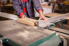 Hands carpenter working with a circular saw. Hands carpenter working on the circular saw Royalty Free Stock Image