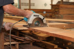 Hands of carpenter is working with a circular saw in carpentry workshop. Royalty Free Stock Image