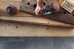 Hands carpenter working a wooden rustic old board with a milling Royalty Free Stock Photo