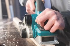 The hands of a carpenter working woodworking power tools. Close up of the work of the electric planer stock photography