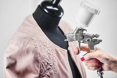 Hands carry out the process of painting a leather jacket on the mannequin Stock Image