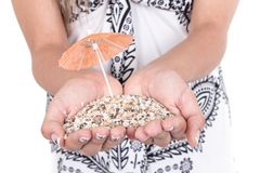 Hands carrying sand with two mini umbrellas Royalty Free Stock Photos
