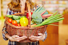 Hands carrying shopping basket. With vegetables in a supermarket Stock Photo