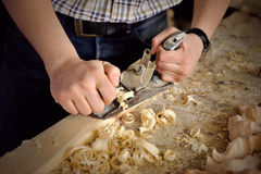 Hands of carver work with jointer in workshop Royalty Free Stock Photo