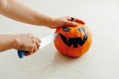 Hands carving jack-o-lantern pumpkin for Halloween. Closeup view Royalty Free Stock Photos