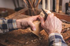 Hands carving a small piece of wood on a workbench royalty free stock image