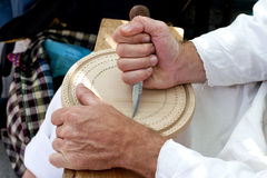 Hands carving in wood. Carver hands carving romanian traditional decorations in wooden  tray Royalty Free Stock Photo