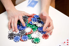 Hands with casino chips making bet or taking win Stock Image