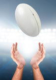Hands Catching Ball. A pair of male hands reaching upwards to catch a rugby ball on a floodlit stadium background - 3D render Stock Images