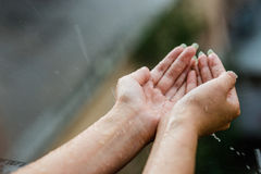 Hands catching clean falling rain drops close up. Environmental and healthcare concept Stock Images