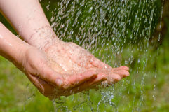 Hands catching clean falling water close up Stock Photos