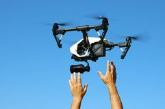 Hands Catching Flying Camera Drone. Picture of a black & white camera drone and hands below about to catch it. Clear blue sky background royalty free illustration
