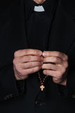 Hands of catholic priest holding rosary. Over black background Royalty Free Stock Photo