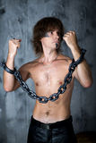 Hands chained. Young handsome man boy model actor hostage slave captive. Art makeup, paint black gray temple chin long hair. Hands chained, desire, call to Royalty Free Stock Images