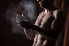 Hands with chalk. Cropped view of a male gymnast dusting his hands with chalk Stock Photo