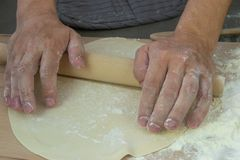 The hands of the chef knead the dough on a wooden table stock photo