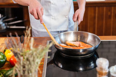 Hands of chef making fresh salmon steak on frying pan. Closeup of hands of chef cook making fresh salmon steak on frying pan on the kitchen Royalty Free Stock Photography