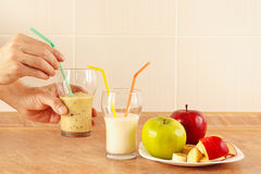 Hands chef offers multifruit smoothie in glasses royalty free stock photo
