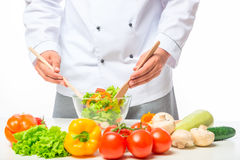 Hands chef stirring with a wooden spoon vegetable salad stock photos