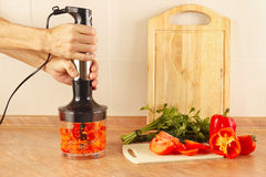 Hands chefs chopped red pepper in blender Stock Photos