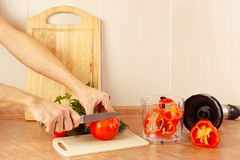 Hands chefs cut red tomato on kitchen table Royalty Free Stock Images