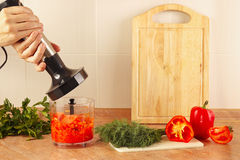 Hands chefs are going to mix red pepper and tomato in blender Royalty Free Stock Images