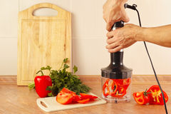 Hands chefs are going to shred red pepper in blender Stock Image